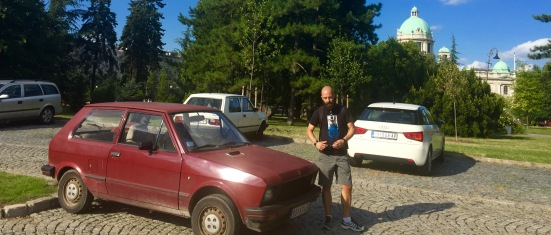 Bruno cun modelo de coche de fabricación serbia. As marcas Zastava e Yugo foron tan populares que incluso eran exportadas a outros países do ámbito soviético. A situación económica obriga a mantelos en bo estado